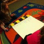 Children measure chart paper with alphabet bean bags.
